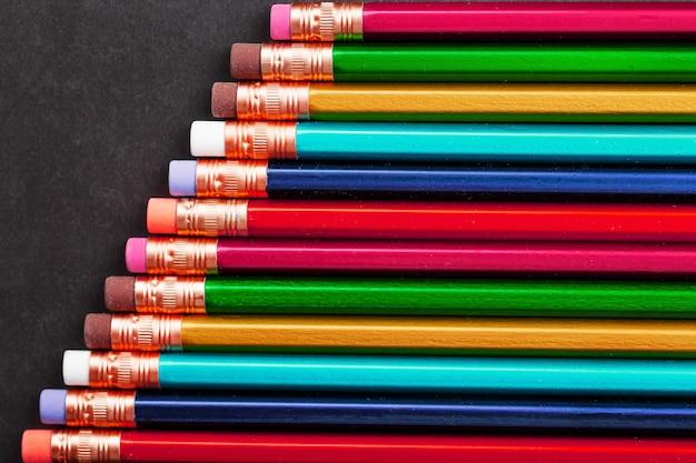 Bleistifte in verschiedenen farben hintereinander auf schwarzem strukturiertem hintergrund.