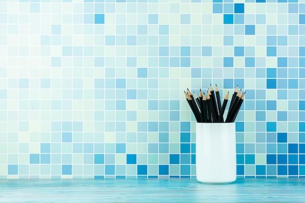 Bleistifte in weißen keramikbechern im blauen büro.