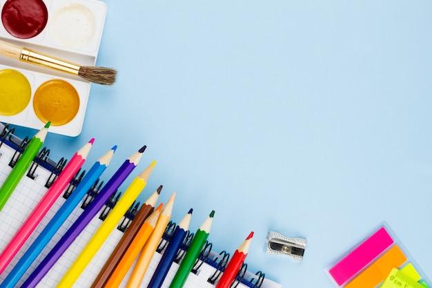 Bleistifte liegen auf einem notizbuch auf blauem grund.