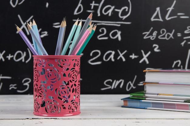 Bleistifte und bücher auf tafelhintergrund mit mathematischen formeln