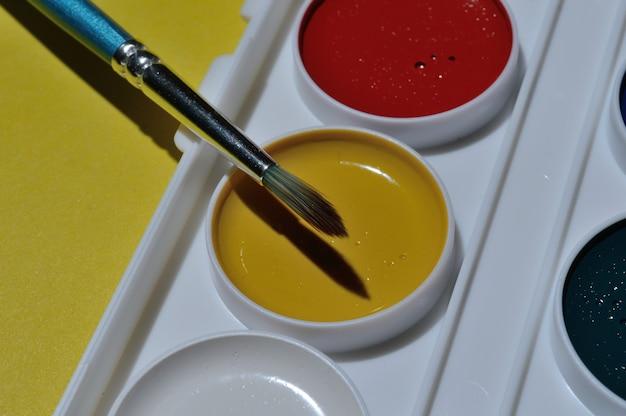 Bleistifte und farben in einer palette auf gelbem grund.