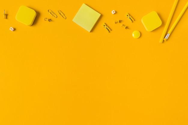 Bleistifte und papierblöcke auf einem gelben tisch