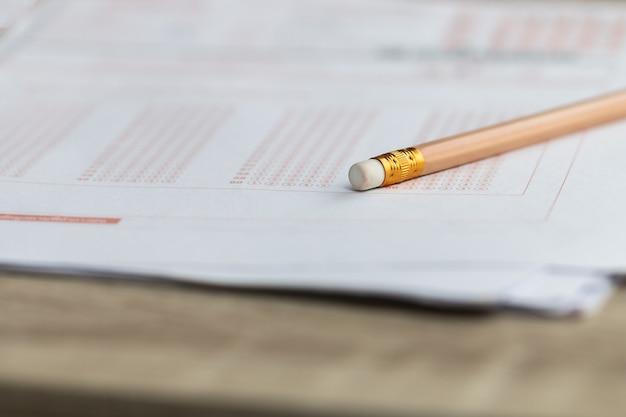 Bleistiftradierer auf standardisiertem testprüfungsformular mit mehreren kohlepapieren mit antworten, die im universitätsklassenzimmer gesprudelt wurden. prüfungswissen im schulkonzept