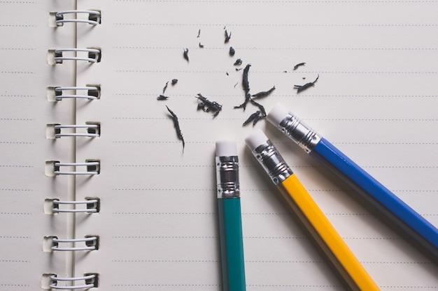 Bleistiftradiergummi, der einen schriftlichen fehler auf einem blatt papier entfernt, löscht, korrigiert und verwechselt konzept.