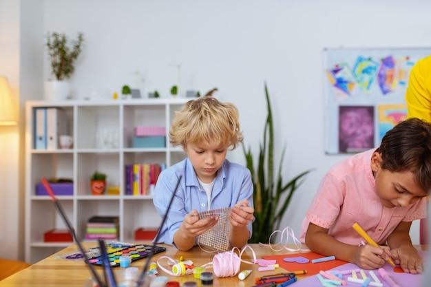 Blick auf aufkleber. blonder schuljunge, der sich aufkleber ansieht, während er im unterricht dekorationen macht