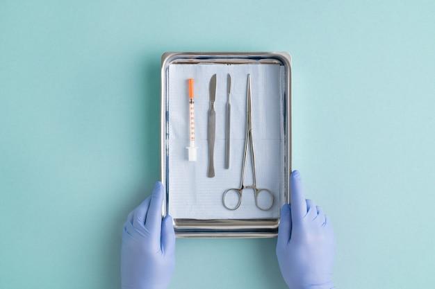 Blick auf behandschuhte hände des chirurgen, der vor der operation eine stahlschüssel mit chirurgischen instrumenten und spritze auf staubigen blauen hintergrund setzt