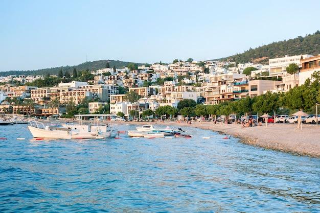 Blick auf bodrum beach, ägäisches meer, weiße häuser, yachthafen, yachten in bodrum stadt türkei bei sonnenuntergang licht.