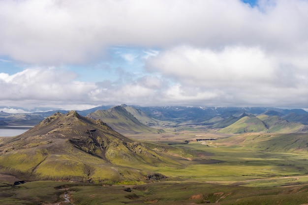 Blick auf das bergtal mit grünen hügeln, flussbach und see