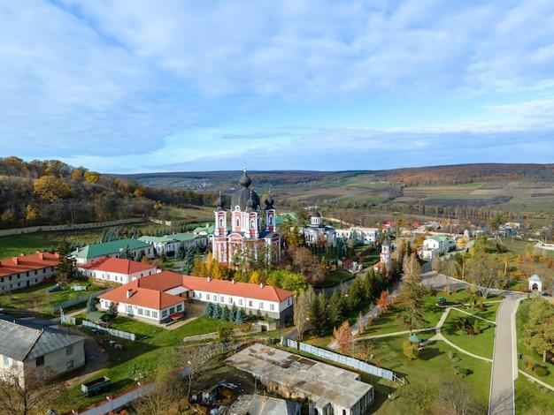 Blick auf das curchi-kloster von der drohne. kirchen, andere gebäude, grüne rasenflächen und gehwege. hügel mit viel grün in der ferne. moldawien