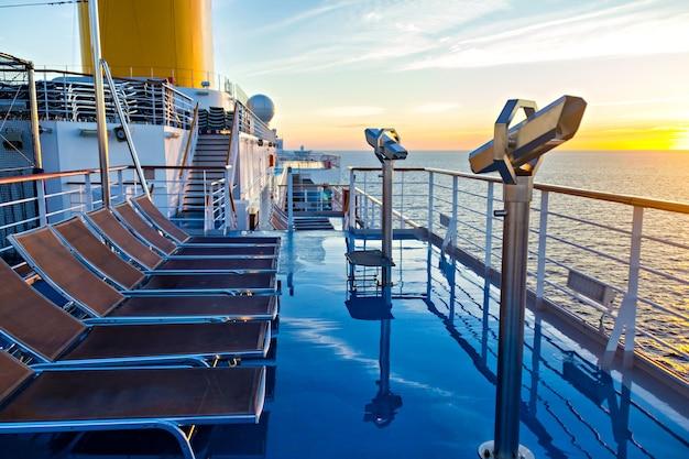 Blick auf das deck des kreuzfahrtschiffes, das meer und den sonnenaufgang