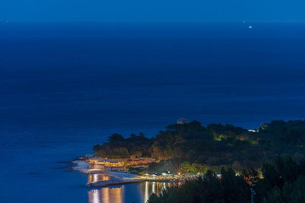 Blick auf das dorf portonovo von oben bei nacht. beleuchtete restaurants und strandresortreflexion auf blauem meer. tourismusziel italien marken