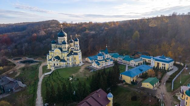 Blick auf das hancu-kloster von der drohne. kirchen, andere gebäude und grüne rasenflächen. hügel mit kahlen bäumen in der nähe. moldawien