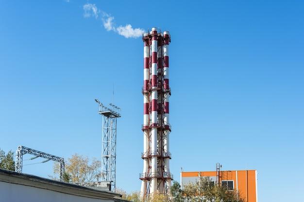 Blick auf das heizkraftwerk weiße dampfwolken steigen aus dem schornstein in den himmel