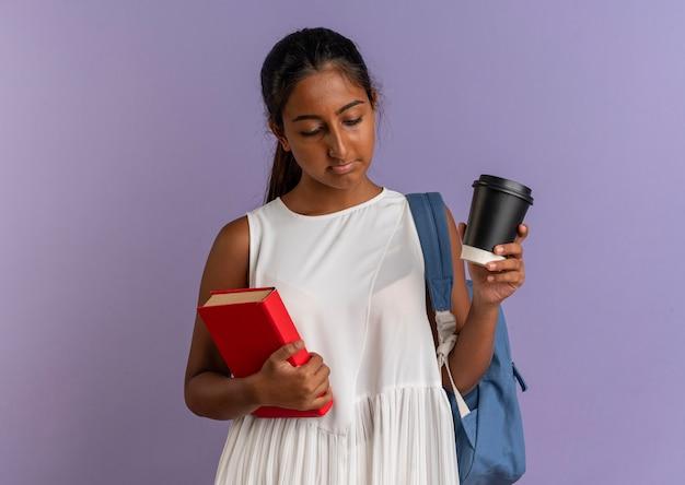 Blick auf das junge schulmädchen, das eine tasche mit einem buch und einer tasse kaffee auf violettem hintergrund trägt
