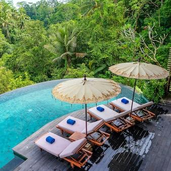 Blick auf das schwimmbadwasser und die sonnenliegen im tropischen dschungel morgens in der nähe von ubud, bali, indonesien, draufsicht