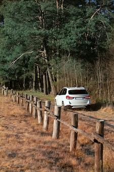 Blick auf das suv-auto an der trail road in der nähe des farm field zauns warmes sonniges licht