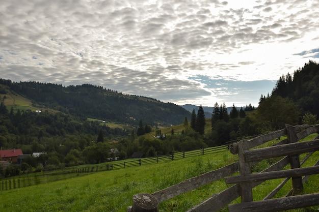 Blick auf das tal von oben auf einem hintergrund grüner berge, blauer himmel mit wolken und bäumen