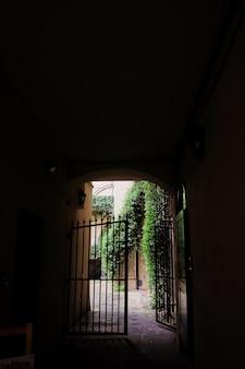 Blick auf das tor im innenhof durch den dunklen torbogen