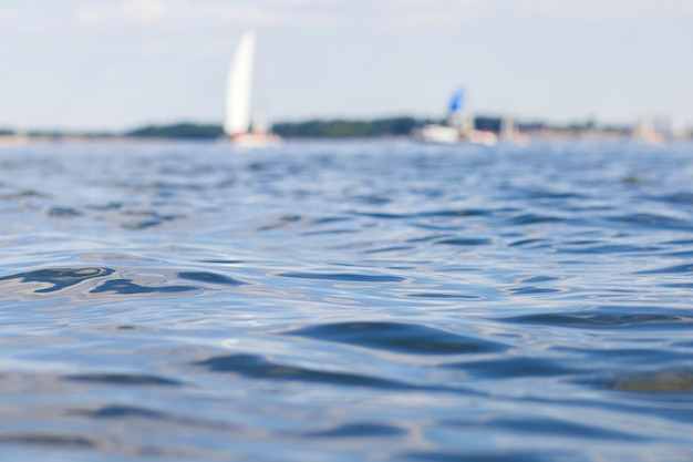 Blick auf das wasser des flusses, verschwommene yachten und boote mit segeln