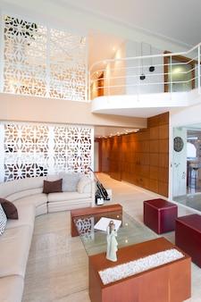 Blick auf das wohnzimmer im haus mit doppelter höhe, haus und dekoration.