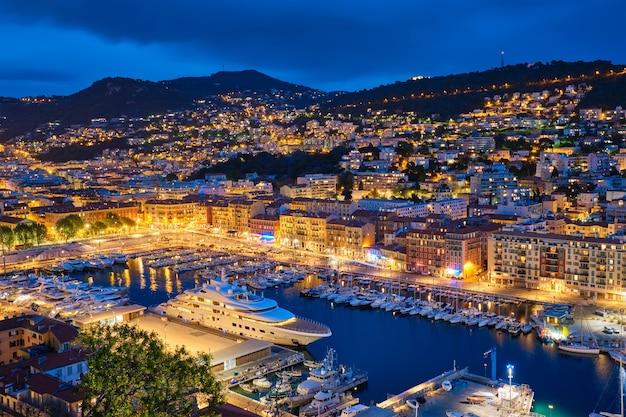 Blick auf den alten hafen von nizza mit luxusyachtbooten von castle hill, frankreich, villefranche-sur-mer, nizza, côte d'azur, französische riviera in der abendlichen blauen dämmerung