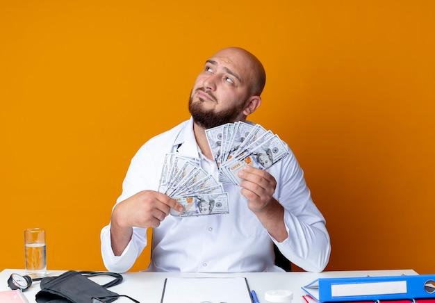 Blick auf den denkenden jungen kahlköpfigen männlichen arzt, der medizinische robe und stethoskop trägt und am schreibtisch sitzt