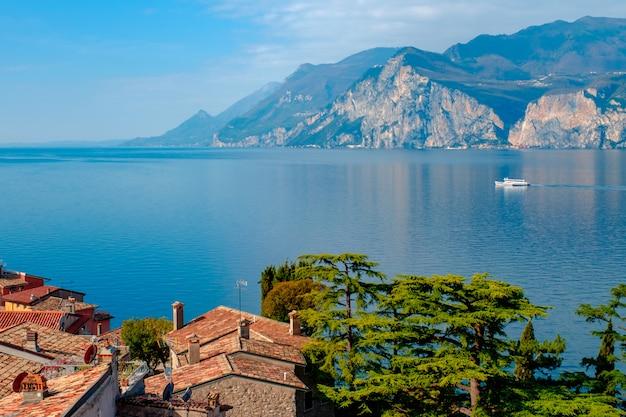 Blick auf den gardasee vom turm in der stadt malcesine. italien. ein blick auf die ziegeldächer der italienischen stadt. gardasee. riva del garda.