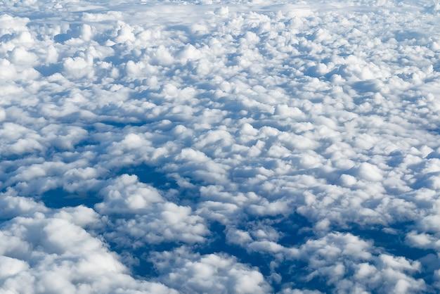 Blick auf den himmel über den wolken blauer himmel hoch blick aus dem flugzeugfenster wolken formt skyclouds back...