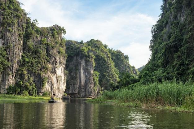 Blick auf den kalksteinberg im tal mit touristischen kreuzfahrten am abend, ngo dong river, ninh binh, halong bay an land