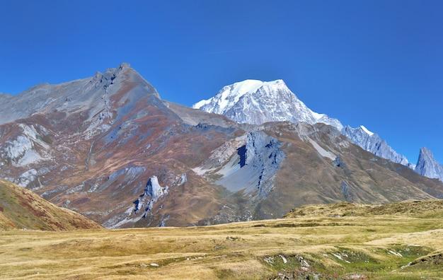Blick auf den mont blanc hinter felsigen berg mit gras bedeckt