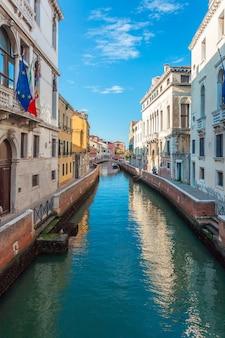 Blick auf den schmalen kanal mit booten und gondeln
