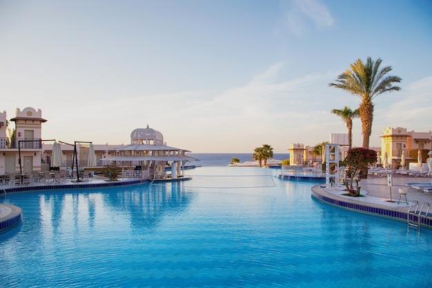 Blick auf den schönen pool mit palmen.