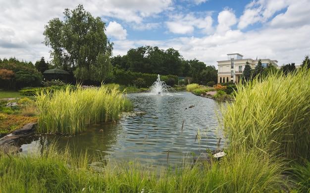 Blick auf den schönen see mit springbrunnen im gartenpark