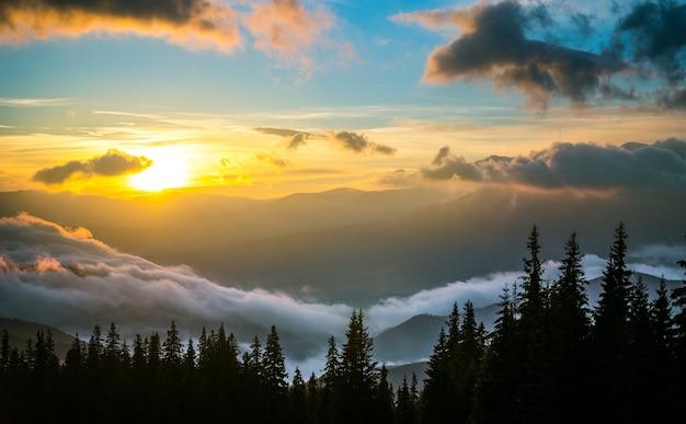Blick auf den schönen sonnenuntergang im gebirgstal. hügel umgeben von wolken mit dramatischem himmel auf hintergrund. konzept der naturschönheit und des sonnenuntergangs.