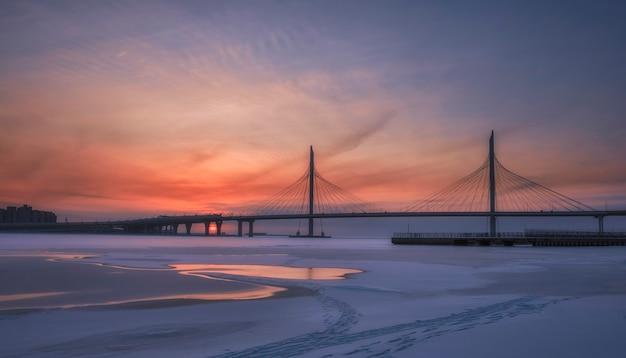 Blick auf den sonnenuntergang der western high-speed bridge diameter. krestovsky insel. hintergrundbeleuchtete winternacht russland, st. petersburg.