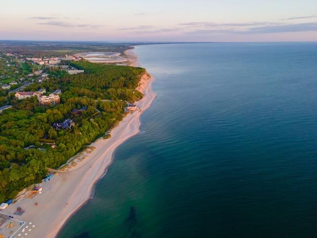 Blick auf den sonnenuntergang von sandstrand, meer und wald an der ostsee in yantarny, region kaliningrad, russland