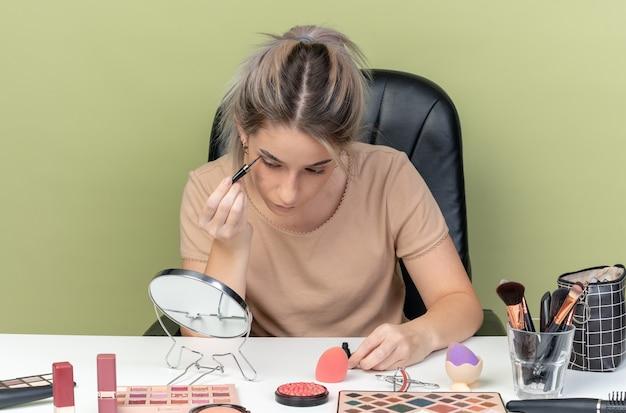 Blick auf den spiegel junges schönes mädchen, das am tisch mit make-up-tools sitzt, zeichnet pfeil mit eyeliner isoliert auf olivgrüner wand