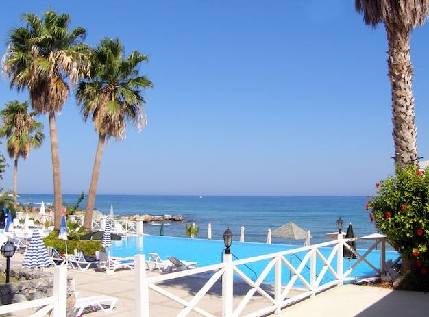 Blick auf den strand an einem sonnigen tag an der mittelmeerküste und einen swimmingpool mit liegestühlen