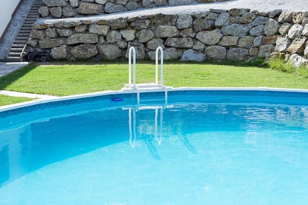 Blick auf den türkisfarbenen pool mit grüner rasenmauer aus steinen und rasenmäher. das konzept von urlaub, landschaftsgestaltung, hauspflege