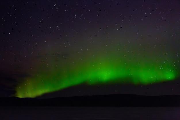 Blick auf die aurora borealis. polarlichter am nächtlichen sternenhimmel über dem see.