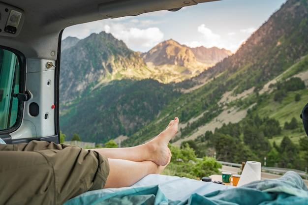 Blick auf die beine eines glücklichen mädchens in einem minivan bei sonnenuntergang