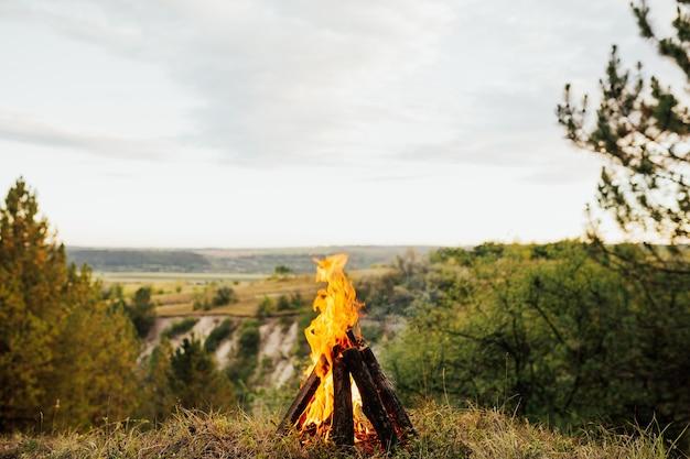 Blick auf die berge mit lagerfeuer an einem sommertag. halten sie nach einem tag voller spaziergänge durch die bergwälder an.