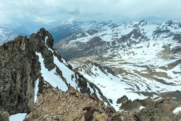 Blick auf die berge von der karlesjoch-seilbahn (3108 m, nahe kaunertal gletscher an der österreichisch-italienischen grenze) mit alpenblüten über abgrund und wolken