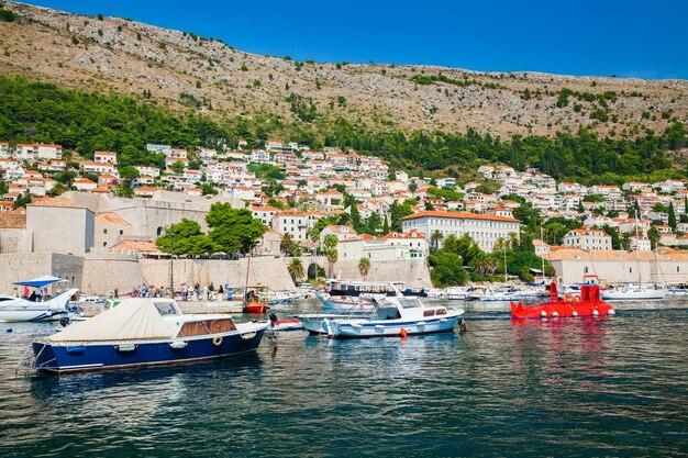 Blick auf die boote am hafen des alten hafens in dubrovnik und auf kleine häuser außerhalb der stadtmauern, kroatien