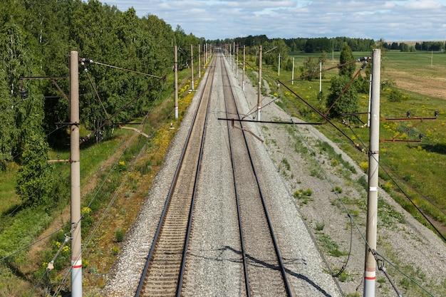 Blick auf die elektrifizierte eisenbahn von der brücke zur leeren eisenbahnstrecke