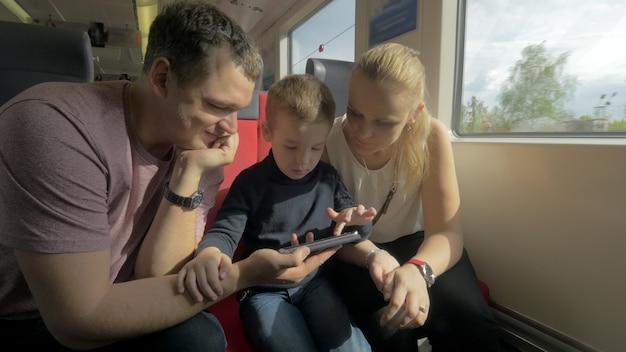 Blick auf die glückliche familie bei der bahnfahrt mit smartphone