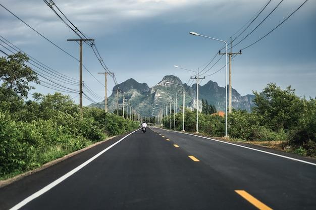 Blick auf die grüne bergkette mit strommast und laternenpfahl auf der autobahn in der landschaft bei sam roi yot, prachuap khiri khan