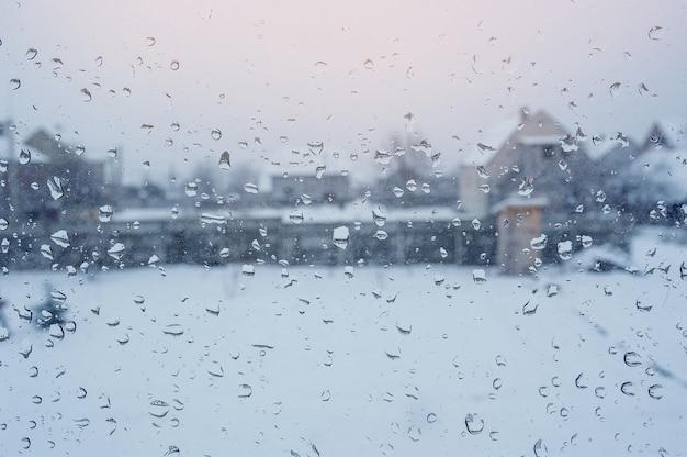 Blick auf die häuser durch ein fenster mit regentropfen