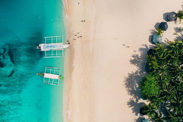 Blick auf die insel daku vom himmel. mann, der sich beim sonnenbaden am strand entspannt. aufnahme mit drohne über der schönen szene. konzept über reisen, natur und meereslandschaften