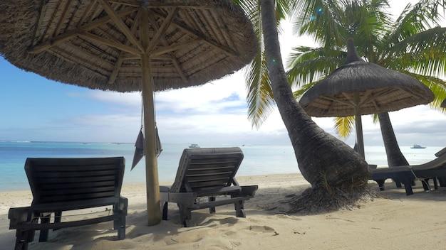 Blick auf die leere chaiselongue in der nähe des einheimischen sonnenschirms und der palmen gegen die insel mauritius mit blauem wasser